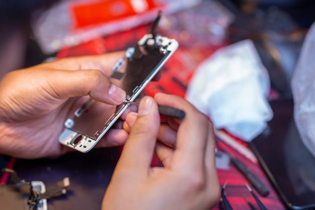 男が携帯電話を修理しています