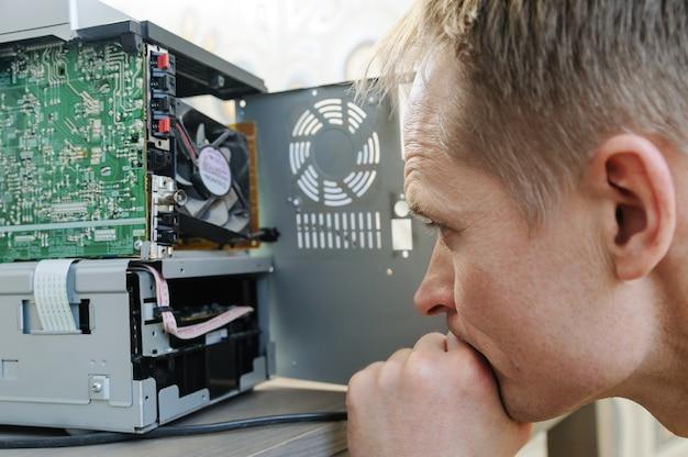 Мужчина ремонтирует музыкальную систему. он смотрит внутрь устройства.