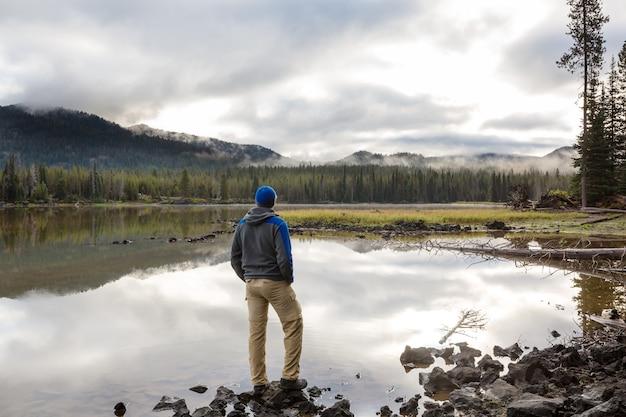 穏やかな湖のほとりで男が安らかに休んでいる。リラクゼーション休暇