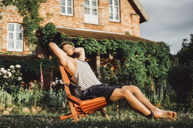 한 남자가 시골집에서 쉬고있다. 수염 난된 남자는 녹색 잔디밭에서 석양을 즐깁니다.