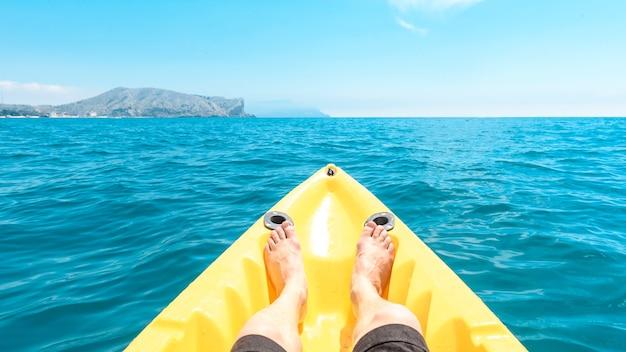 美しい景色を見ながら海でボートに乗って休んでいる男性。夏の旅行のコンセプト