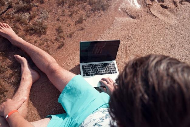 男はラップトップで砂の上に座って、フリーランサーとして働いています