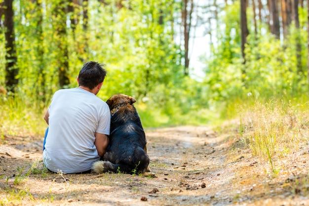 Мужчина сидит с собакой на тропинке в лесу