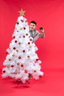 한 남자가 크리스마스 트리 옆에 서 있다