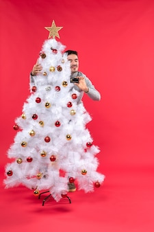 クリスマスツリーの横に男が立っています