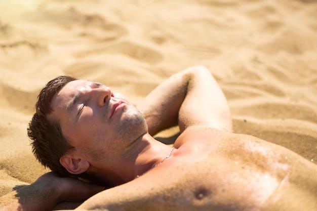 Мужчина загорает на раскаленном желтом песке. пляжный отдых, курорт на берегу моря. защита от солнца, уф-лучи, солнцезащитный фильтр, spf. здоровье кожи