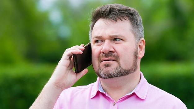 男が電話のクローズアップで話している男が彼の耳の近くにスマートフォンを持っています