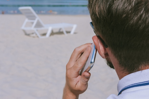 男が浜辺で電話で話している。砂を背景に、水辺の長椅子。