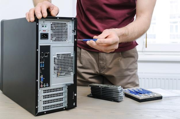 男はデスクトップ内部にアクセスするためにネジをほどいています。