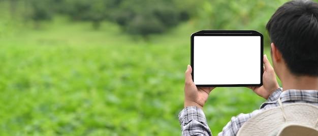 男は背景として芝生のフィールドの上に座っている間、白い空白の画面のコンピュータータブレットを使用しています。