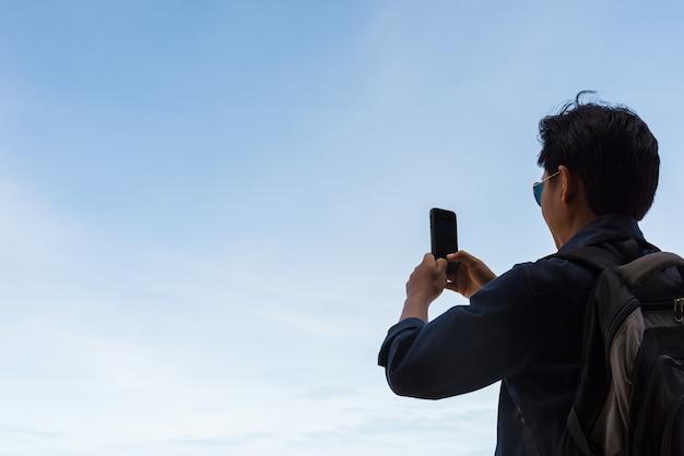 Мужчина использует мобильные телефоны для съемки и синего неба