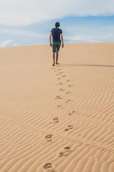 男がベトナムの砂漠、ムイネーを歩いている