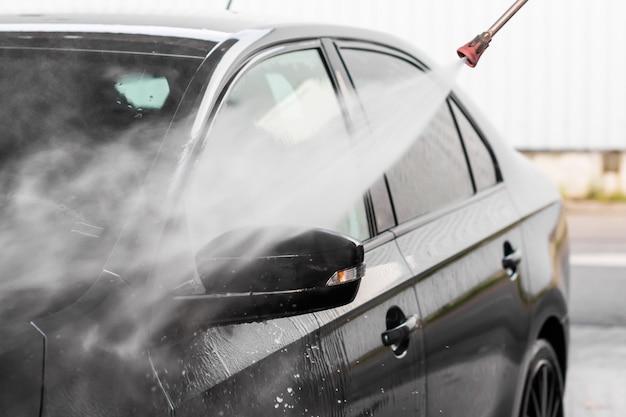 Мужчина моет машину у автомойки самообслуживания. мойка машины под высоким давлением промыть водой. оборудование для автомойки, млада болеслав,