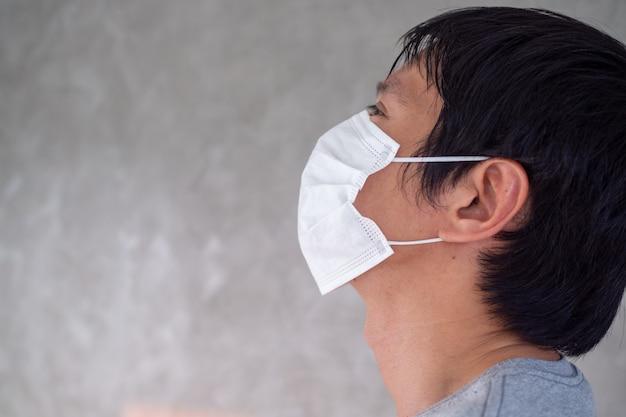 世界中に広まっているcovid-19ウイルスを防いだり、pm2.5を防いだりするために男性がマスクを着用しています。致命的な感染を防ぐには、誰もが手を取り合って行動する必要があります。