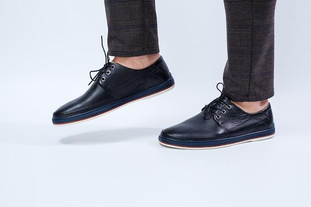 한 남자가 레이스에 천연 가죽으로 만든 고전적인 검은색 신발, 비즈니스 스타일의 남성용 신발을 신고 있습니다. 고품질 사진
