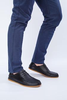 한 남자가 레이스에 천연 가죽으로 만든 고전적인 검은색 신발, 비즈니스 스타일 아래 남성용 신발을 신고 있다