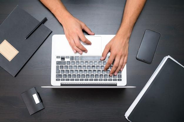 남자는 빈티지 나무 테이블에 랩톱 컴퓨터를 사용하여 작동합니다. 키보드를 입력하는 손.