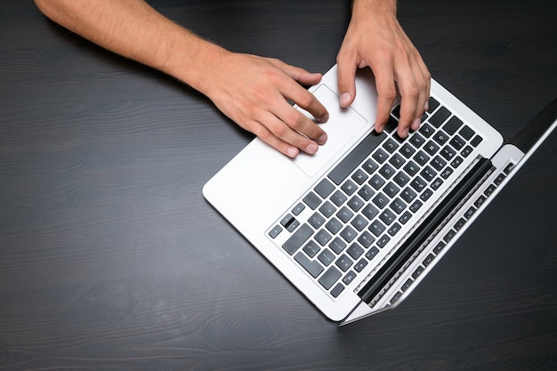 Мужчина работает с портативным компьютером на старинном деревянном столе. руки печатают на клавиатуре. вид сверху, рабочее место в офисе