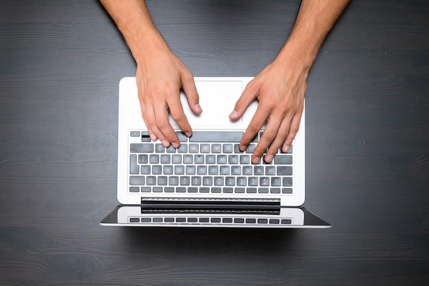 男性は、ヴィンテージの木製テーブルでラップトップコンピューターを使用して作業しています。