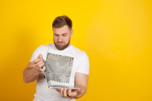 男は冗談めかして、コピースペースがあり、黄色の背景でラップトップを開けません。新しい近代的なテクノロジー、ガジェット、およびコンピューターの概念。