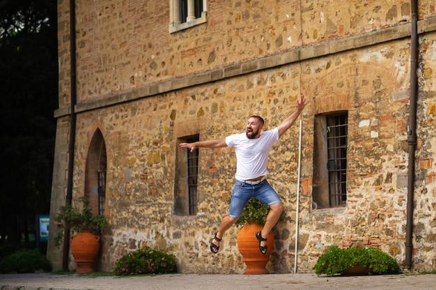 한 남자가 투스카니의 카스티 글 리온 첼로에 위치한 중세 성 파 스키니 성 근처에서 점프합니다. 이탈리아