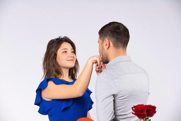 Мужчина целует руку девушки, держащей за спиной букет красных роз на сером фоне. концепция дня святого валентина.