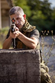 軍服を着たエアガンのアサルトライフルでカバーの後ろにひざまずく男