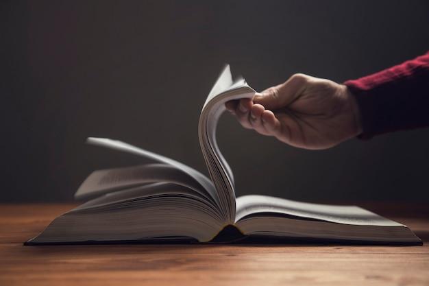 Мужчина листает страницы книги на темной поверхности