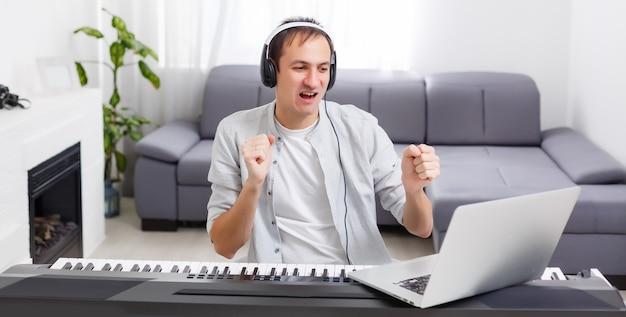 집에 있는 컴퓨터로 온라인으로 피아노 연주를 배우는 남자. 독학, 집에 머물며 온라인 작업의 개념
