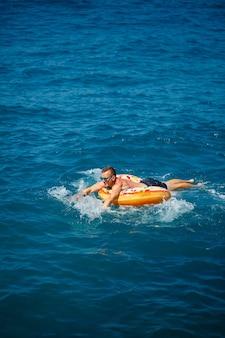 Мужчина лежит на большом надувном резиновом круге и плывет по синему морю в яркий солнечный летний день.