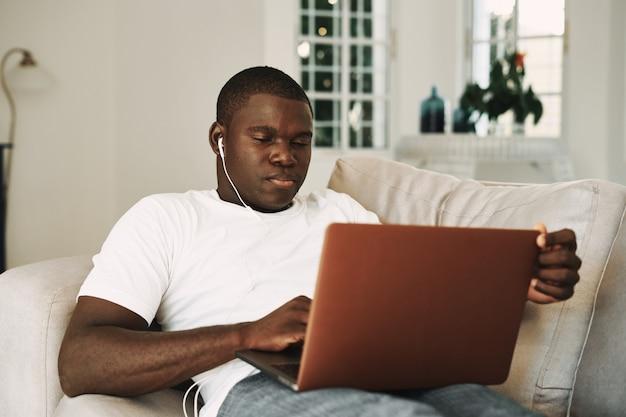 ヘッドフォンのラップトップでソファに横になっている男