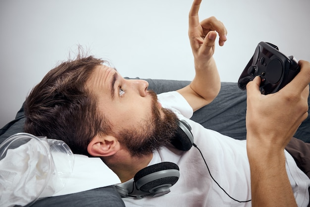 남자는 레저 라이프 스타일을 재생 게임 패드 헤드폰으로 소파에 놓여 있습니다.