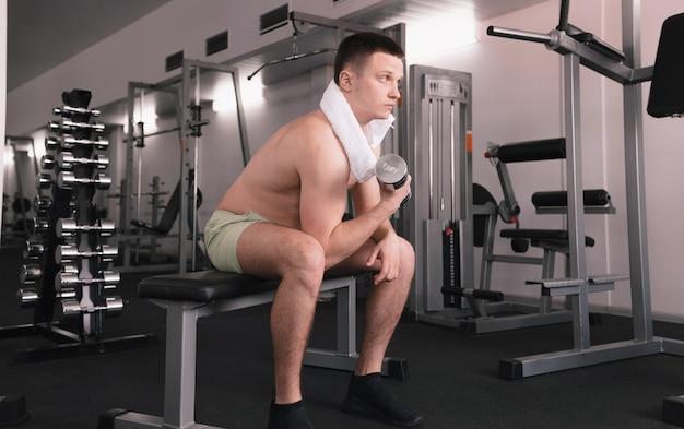 한 남자가 피트니스 룸에서 아령을 들어 올립니다. 한 남자가 스포츠 센터에서 스포츠를합니다. 사람은 자신의 건강에 관심이 있습니다. 벌거 벗은 몸통