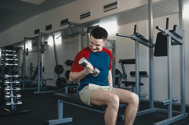 남자는 체육관에서 반짝이 아령을 들어 올립니다. 한 남자가 스포츠 센터에서 스포츠를합니다. 사람은 자신의 건강에 관심이 있습니다.