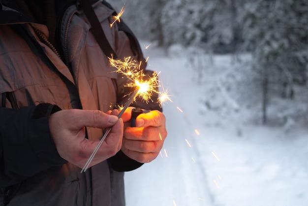 Мужчина зажигает бенгальские огни в зимнем лесу.