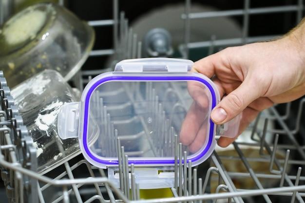 Мужчина загружает в поддон посудомоечной машины грязную посуду, тарелки, ложки, вилки, столовые приборы.