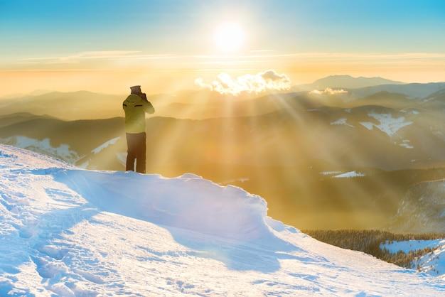 雪と冬の山々の太陽と美しい夕日を見ている男