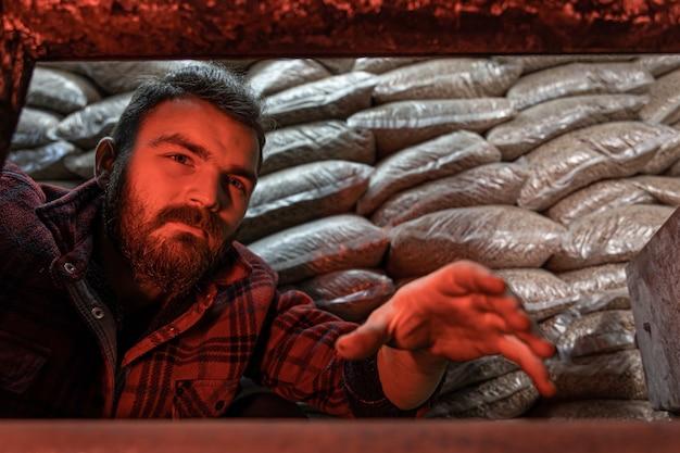 Мужчина смотрит в котел на твердом топливе с открытой дверью котла с пламенем огня