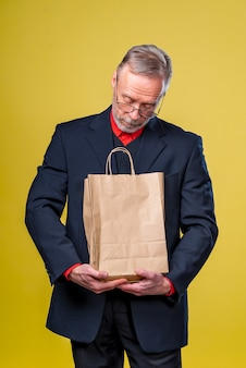 Мужчина смотрит на бумажный пакет, получающий подарок.