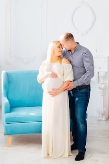 Мужчина смотрит на свою беременную жену и обнимает