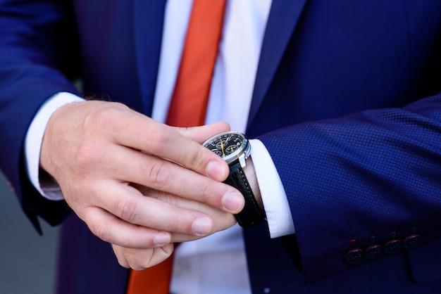 男が時計を見る。時間です。