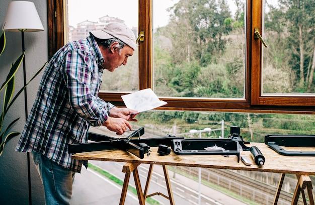 男性は、在宅勤務用のオフィスチェアキットを組み立てるための取扱説明書を見ています。