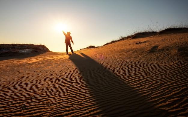 남자는 저녁에 태양을 봅니다. 영웅은 그의 손에 태양을 들고 있다