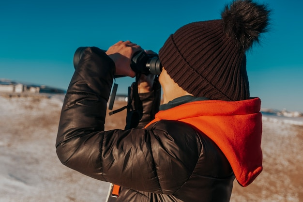 한 남자가 쌍안경을 통해 자연을 본다. 산에서 쌍안경으로 관광.
