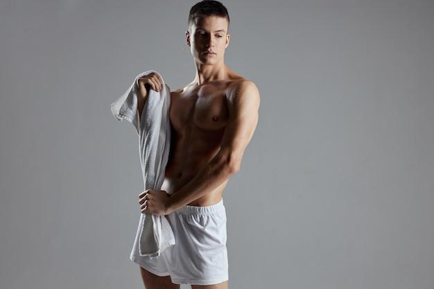 男は灰色の背景のボディービルダーのショートパンツの手でタオルを作った