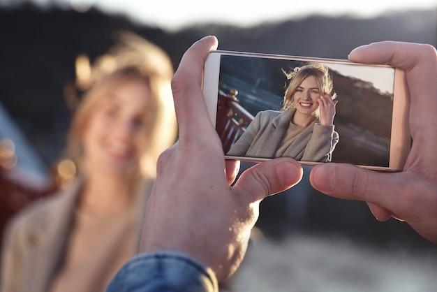 晴れた春や秋の屋外で橋の上に立っている幸せな笑顔の女性の電話で男性が肖像画を作る