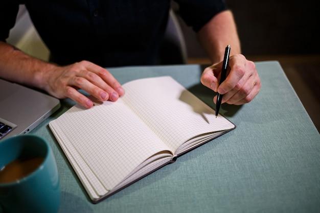 男はノートにペンで記録を作ります。重要事項を記録するための本。ビジネスマンの日記