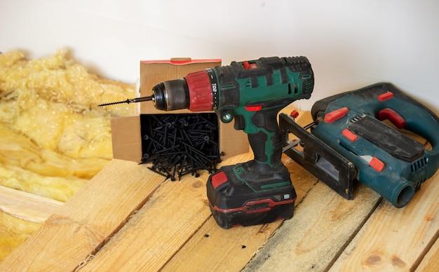 남자는 집, 드라이버, 나사, 톱을 수리합니다. 나무 바닥. 선택적 초점