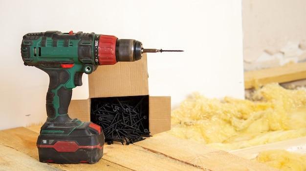 남자는 집, 드라이버, 나사, 톱을 수리합니다. 나무 바닥.