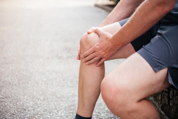 膝蓋大腿関節痛に苦しんでいる間に膝蓋骨をマッサージしている男性